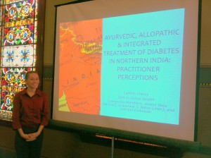 alum Camille Clancy defending her thesis on Ayurveda and integrative medicine in India this past spring.