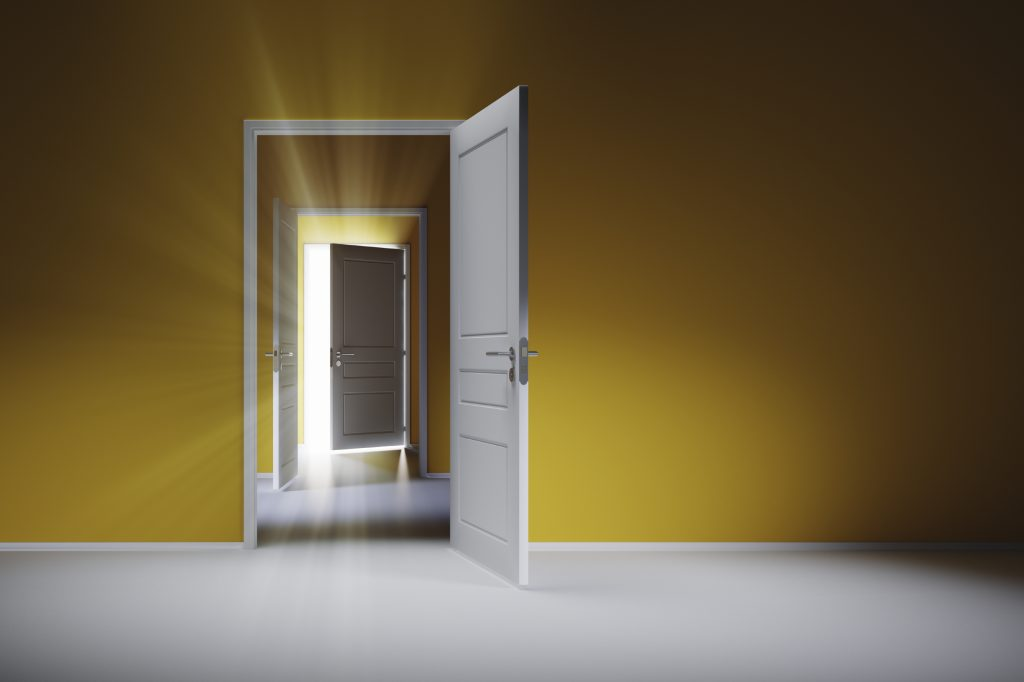Three open white doors on the yellow wall. Rays of light shine through the open door.