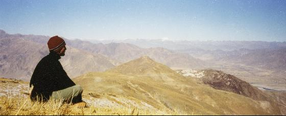Person sitting on a mountaintop staring out into the distance
