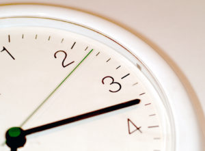 Close up of an analog clock showing the minute hand