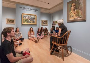 Students of the Museum anthropology class sit on the floor of the Fleming's Wolcott Gallery while listening to a guest lecturer.