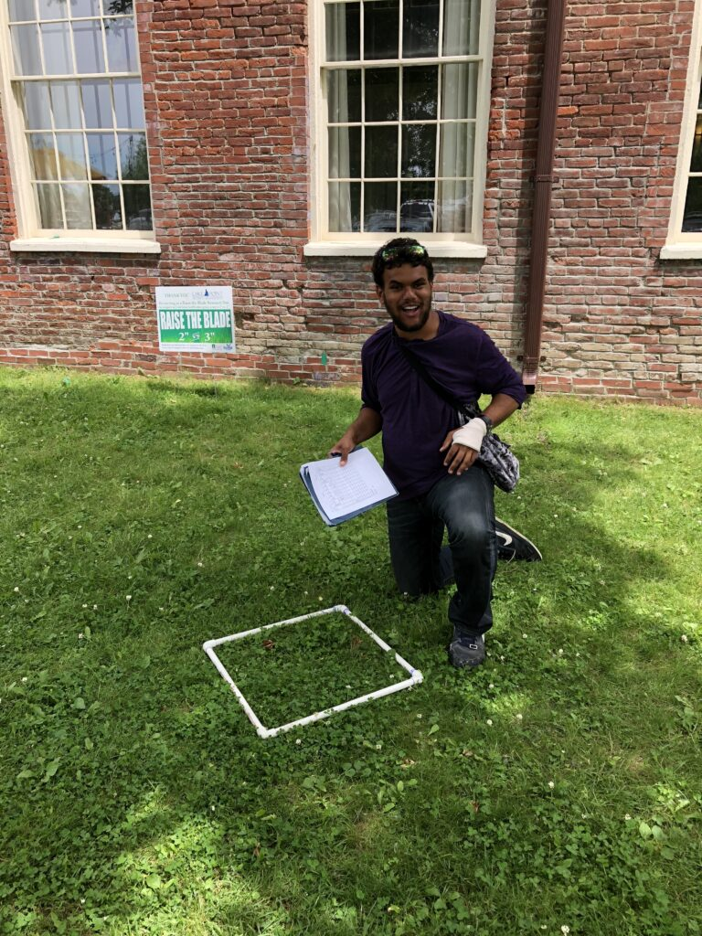 Photo of a student with a 1 m square quadratic lying on the grass