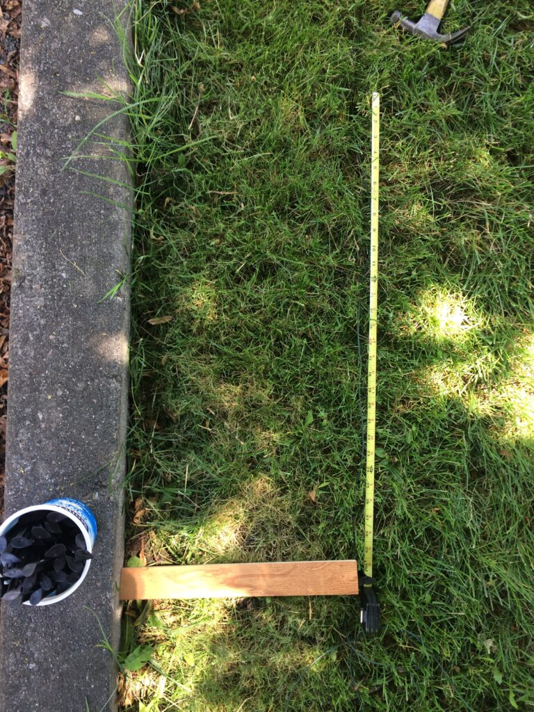 """Overhead picture of a piece of wood and a measuring tape measuring 14"""" and 24"""" , respectively."""