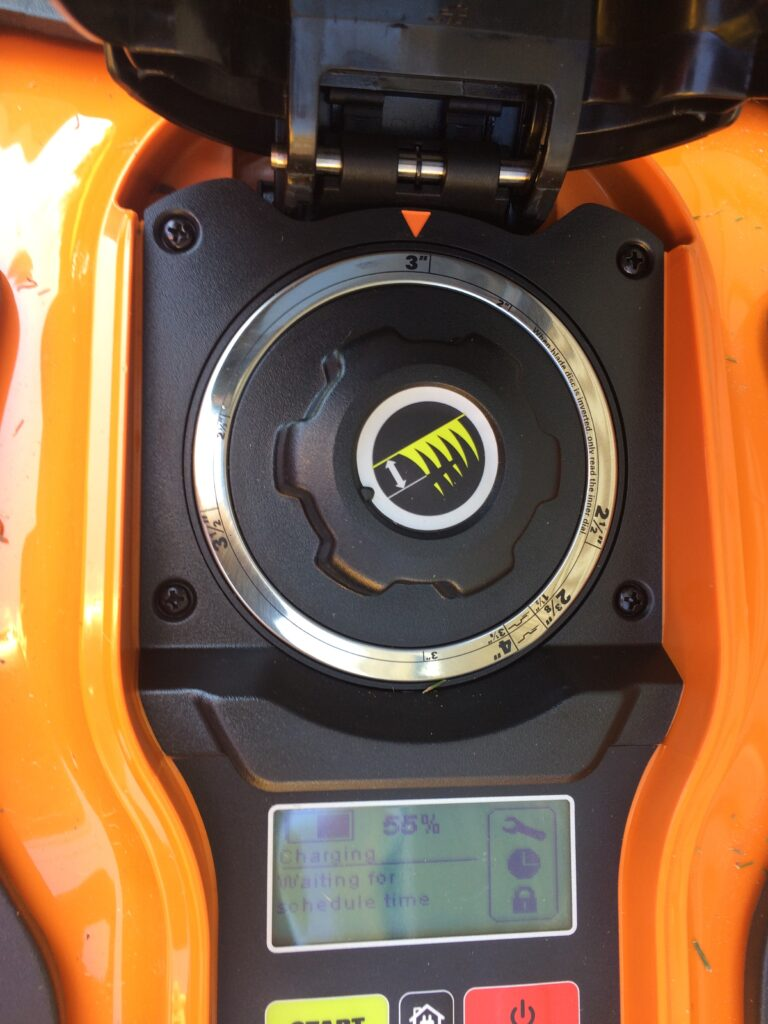 Photo of the inside of a robotic mower where the length of grass height to cut to is set by a dial.