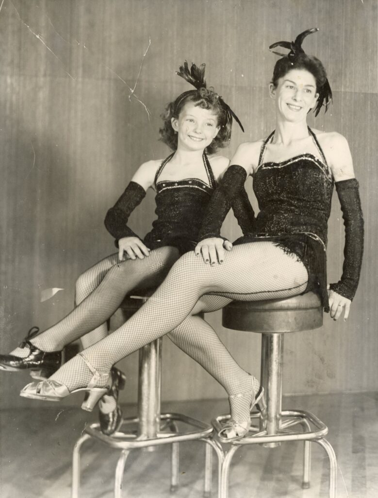 Polly Nulty and her daughter Mary in matching dance costumes and tap shoes pose on stools.