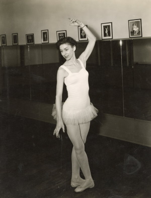 Polly Nulty, wearing a leotard with tutu and ballet shoes, demonstrates a dance position.