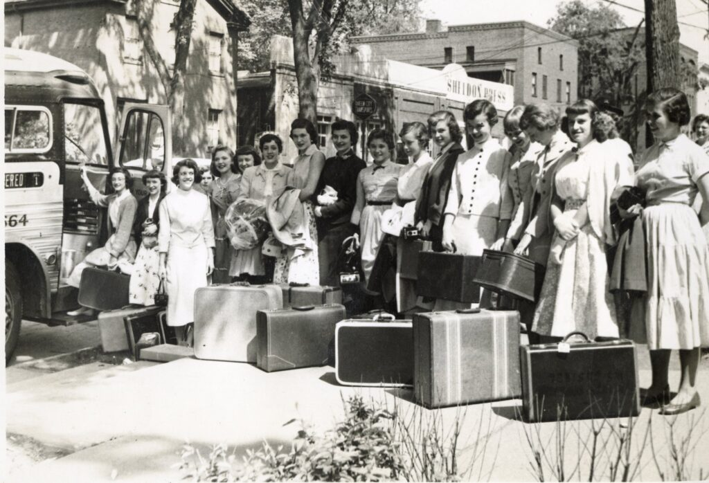A group of young women with suitcases get ready to get on a bus.