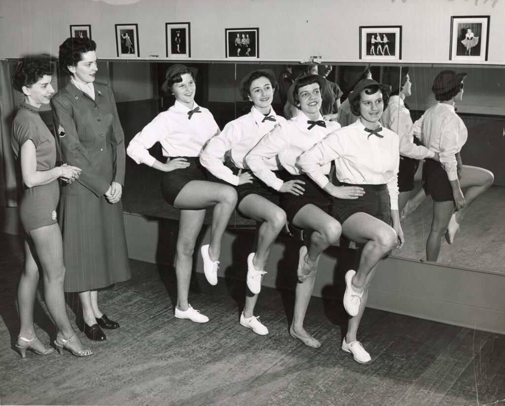 A dance instructor and a woman drill seargeant in uniform look at four you women dancers practicing in the Nulty studio.