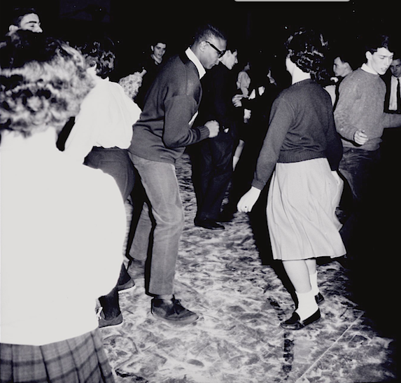 Photograph of a male and female student dancing a crowd of other students.