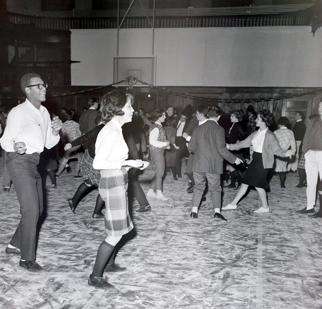 Photograph of a male and female student walking in the gym while smiling and snapping their fingers. Other students dance in the background.