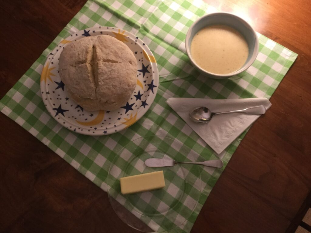 Loaf of homamde bread and bowl of cheese soup