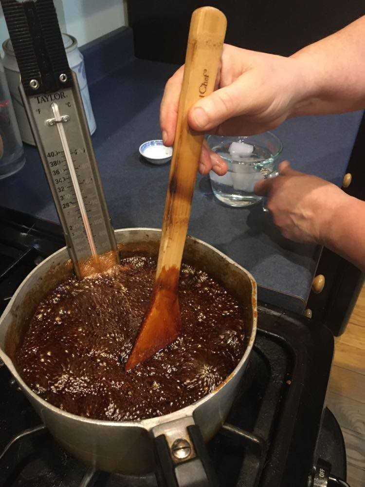 Cook stirs a pot on a stove holding the boiling molasses mixture and a thermometer.
