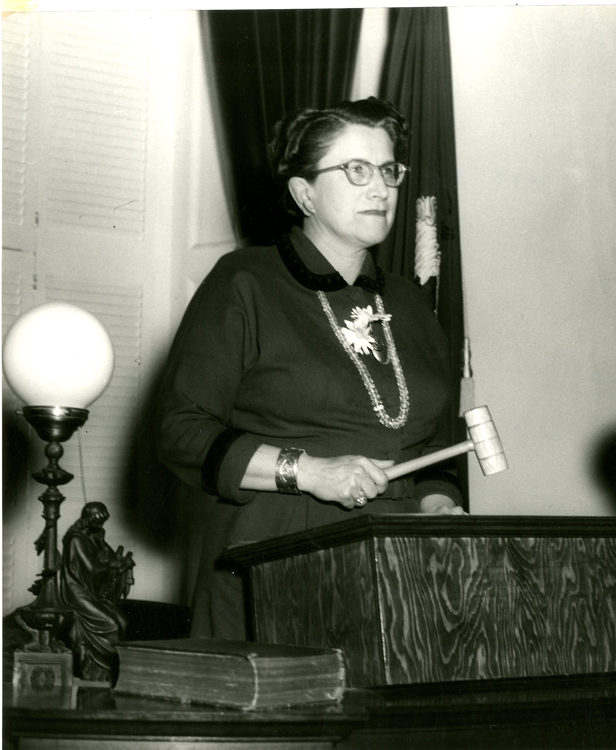 Consuelo standing at a podium holding a wooden gavel.