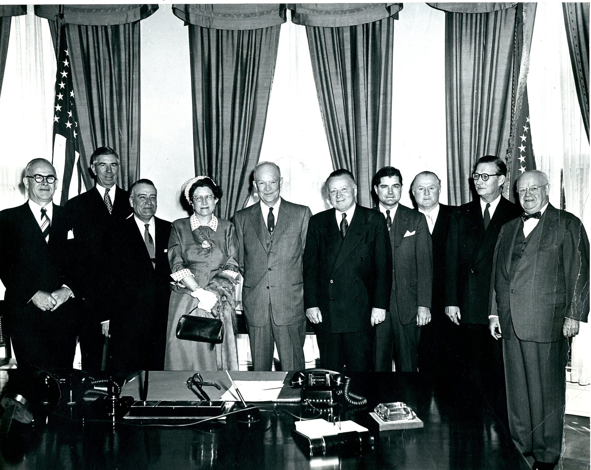 A group portrait showing several men wearing suits as well as Consuelo Northrop Bailey and President Eisenhower in the center. Everyone is looking at the camera and smiling. The President's desk is visible in the foreground while two flags and several window treatments are apparent in the background.