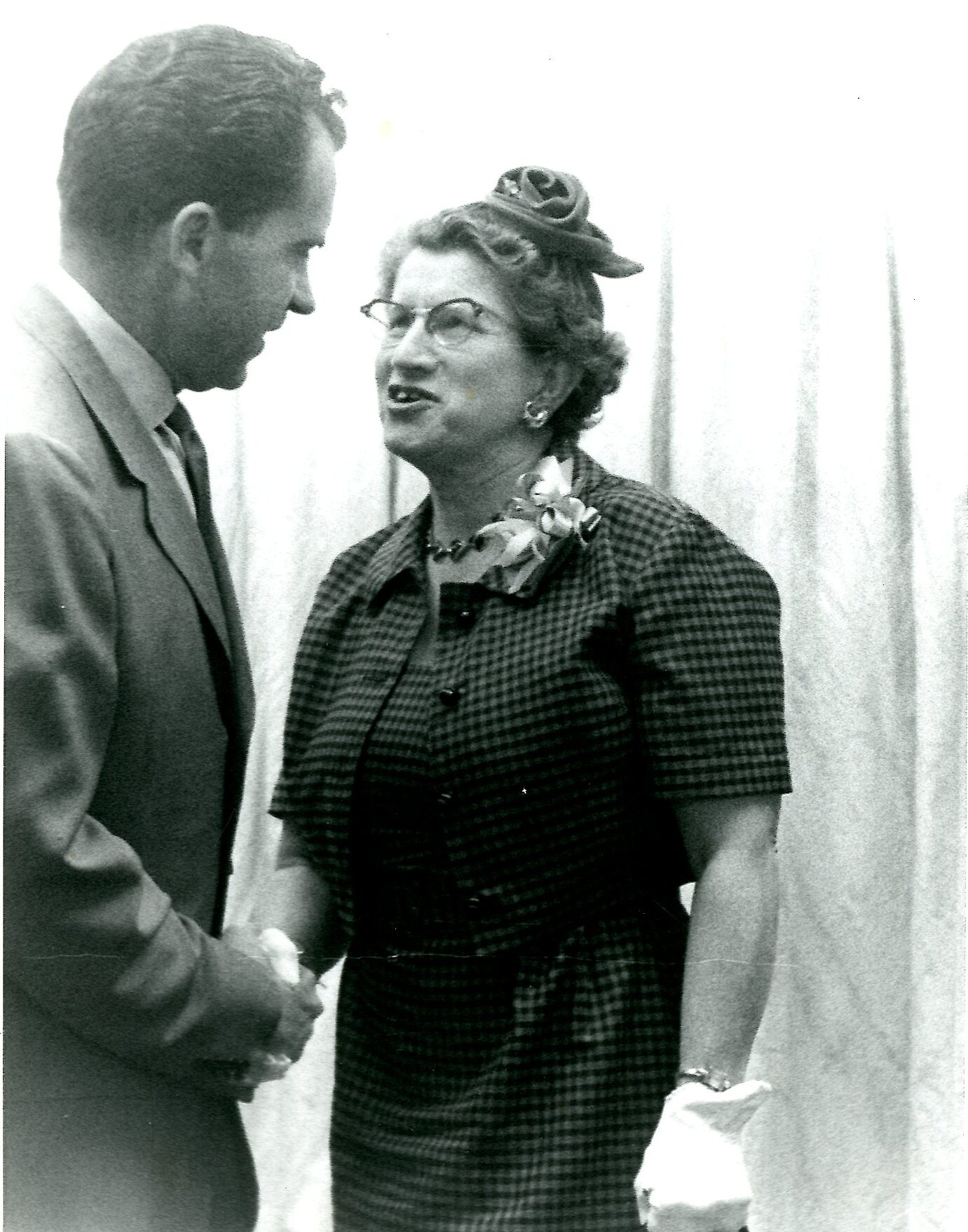 A photograph of Richard Nixon, visible in an obscured profile, stood shaking hands with Consuelo Northrop Bailey in front of a light-colored curtain. She appears to be speaking and he is gently smiling; they are both making eye contact with each other.