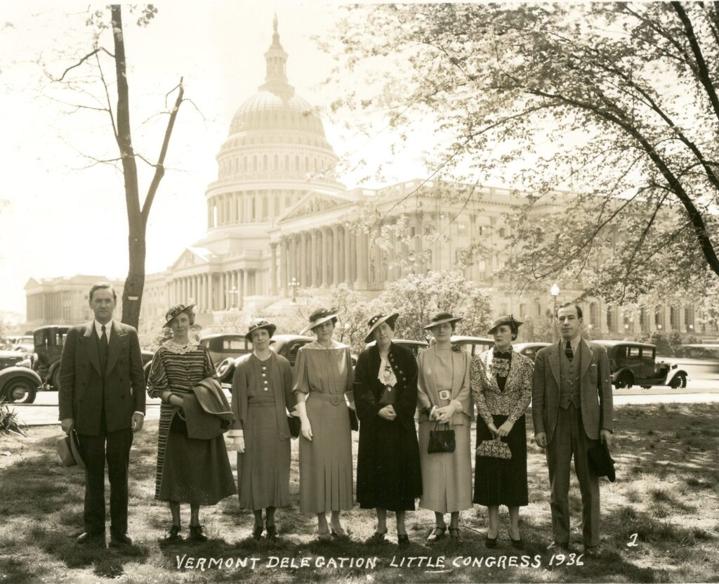 A photograph of eight adults (six women flanked by two men) standing shoulder to shoulder with the capitol building in Washington, D.C. in the background The men wear dark three piece suits with ties and hold their hats while the women wear skirts suits or long sleeved dresses, hats, and gloves.