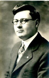 A formal portrait of a man wearing a suit and round glasses