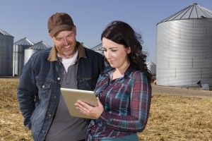 A royalty free image from the farming industry of a farmer couple using a tablet computer.